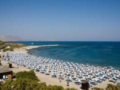 Солнечный пляж с большим количеством зонтиков, Родос, Греция