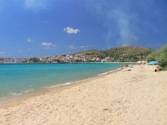 4 young people under an umbrella on Neos Marmaras beach, Halkidiki Greece