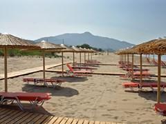 Соломенные зонтики и лежаки на песчаном пляже Закинфа