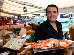 64_A-Greek-fish-taverna-waiter-showing-off-a-lobster-at-a-restaurant-in-Crete,-Greece