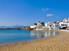 14_The-famous-Tavern-on-the-sea-mirror-of-the-bay-of-the-island-of-Mykonos-with-a-red-boat-and-the-church
