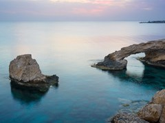 Каменная арка и скалы в море после захода солнца возле Айя-Напа